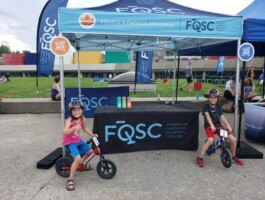 Le kiosque de la FQSC et une participante à la course de vélo-trotteurs